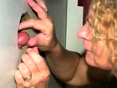 Slutty mature lady with glasses worships glory hole cocks