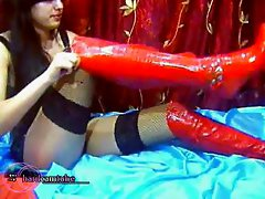 High heeled girl in stockings and latex plays with a gag ball